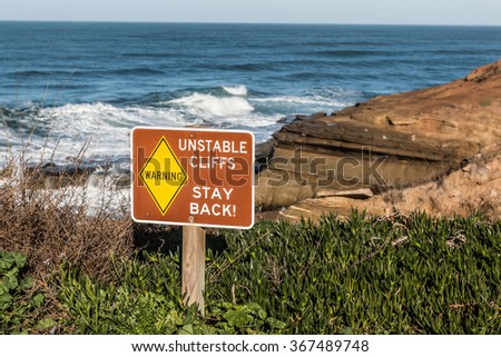 Danger sign with cliffs in background at Sunset Cliffs in San Diego, California - stock photo