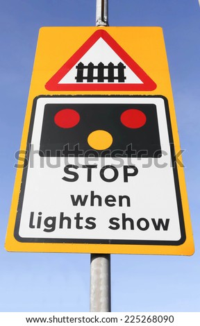 Danger, stop when lights show, a railway crossing roadsign against a blue sky background - stock photo