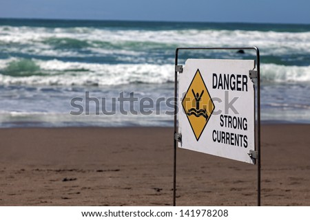 Danger - strong currents. Sign seen on the beach in New Zealand. - stock photo