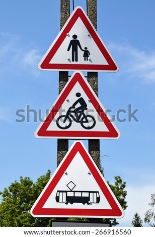 Danger, tram car, bicycle and pedestrians traffic signs next to the road - stock photo