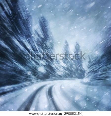 Danger turn at the heavy snowfall road. Motion blur visualizies the speed and dynamics. - stock photo
