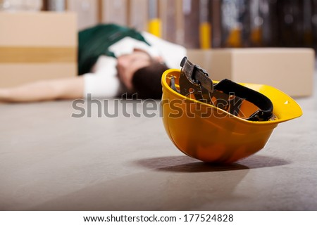 Dangerous accident in warehouse during work - wounded worker - stock photo