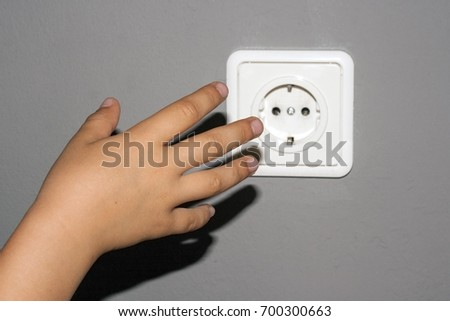 Dangerous behavior of the child with electricity. Children's hand reaches for an electrical outlet