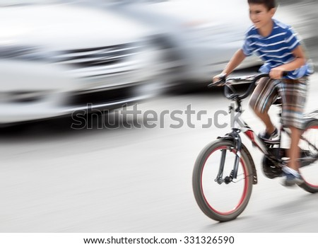 Dangerous city traffic situation with a boy on bicycle and cars in motion blur. Intentional motion blur - stock photo