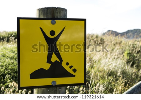 Dangerous cliff sign/ a yellow and black sigh indicating that the cliffs are unstable - stock photo
