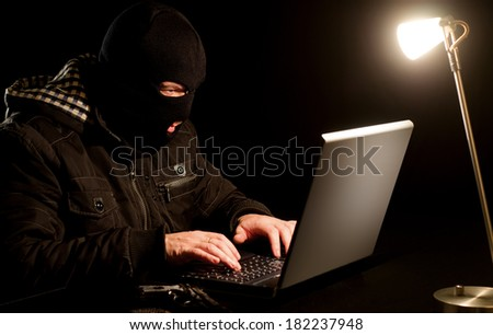 Dangerous criminal trying to crack password protected notebook. - stock photo