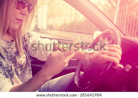 dangerous driving young lady sending text messages with phone on one hand and the other on steering wheel pinkish vintage filter - stock photo