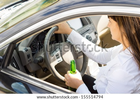 Dangerous drunk and inebriated female driver holding her her steering wheel in one hand and bottle of alcohol in the other as she drives - stock photo