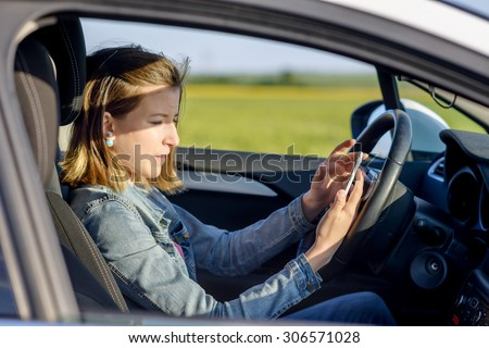 Dangerous female driver reading a text message on her smartphone and taking her attention off the road, profile view - stock photo