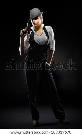 Dangerous girl with gun on black - stock photo