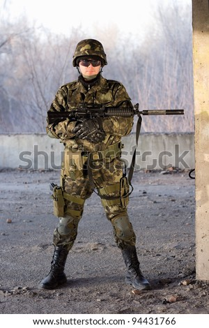 Dangerous guy holding a rifle in abandoned house - stock photo