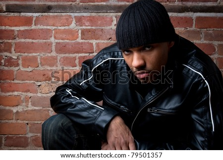 Dangerous looking guy dressed in black, sitting near a brick wall. - stock photo