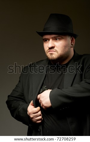 Dangerous man in black suite and hat with gun. - stock photo