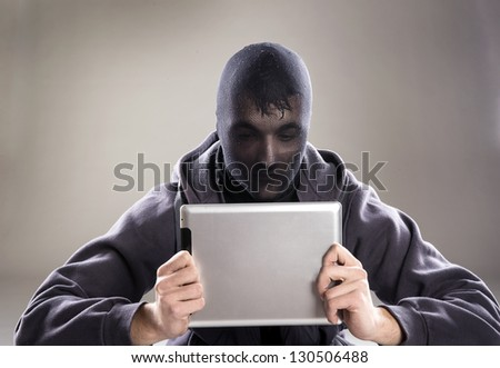 Dangerous man in mask with tablet on isolated background - stock photo