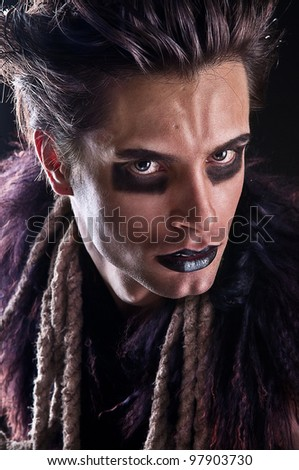 dangerous man watching, aggressive makeup on his face - stock photo
