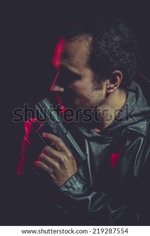 dangerous man with a gun and black leather jacket - stock photo