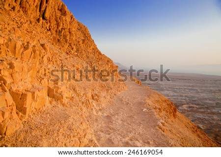 Dangerous path on the mountain slope in Negev desert at sunset - stock photo