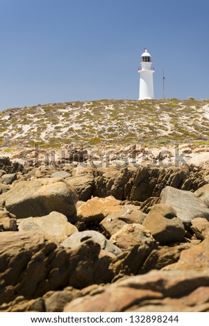 Dangerous rocks surround the lighthouse at Corny Point, South Australia. - stock photo