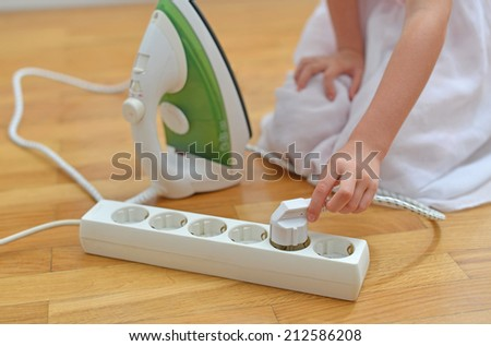 Dangerous situation at home. Child playing with electricity. - stock photo