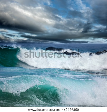 Dangerous stormy weather - dramatic dark clouds and big ocean waves, focus in the front