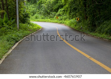 Dangerous turn on wet asphalt road with forest at a rainy day. Curve of the road in green tropical forest. Dangerous turn on wet road. Empty road. Bali road in a forest. Road turn. Summer road scene.