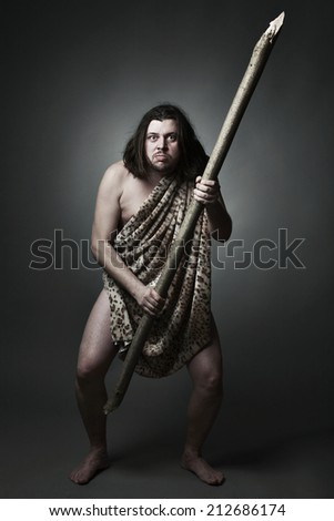 Dangerous wild man in skin of beast threaten with big stick. - stock photo