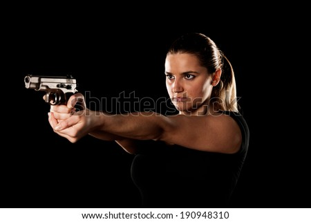 Dangerous woman terrorist dressed in black with a gun in her hands