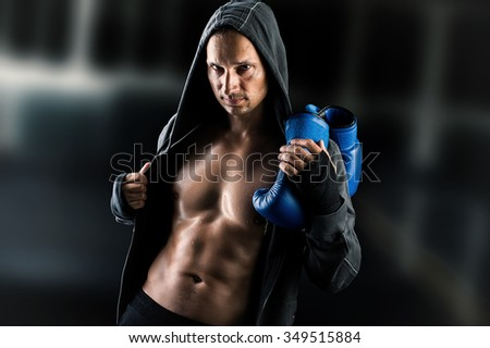 Dangerous Young muscular man boxer wearing jacket with hood. Boxing gloves slung over his shoulder on dark background indoor. - stock photo