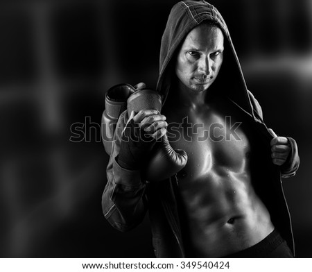 Dangerous Young muscular man boxer wearing jacket with hood. Boxing gloves slung over his shoulder on dark background indoor. Black and white - stock photo