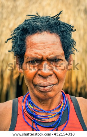 Dani circuit, Indonesia - September 2015: Older native woman dressed in orange shirt posing and frowning in Dani circuit near Wamena, Papua, Indonesia. Documentary editorial.