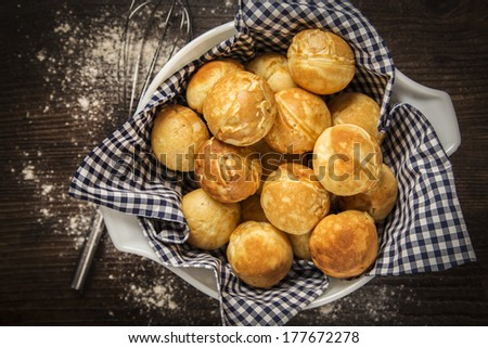 Danish Ebelskiver Pancakes Served in a bowl with a blue and white gingham napkin on a wood table top - stock photo