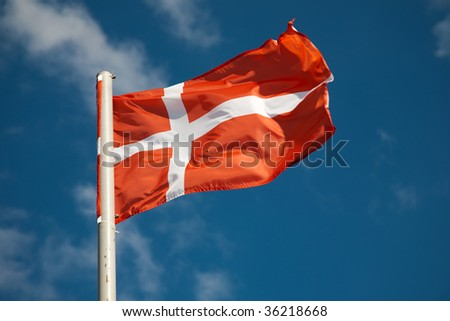 Danish flag against blue sky - stock photo