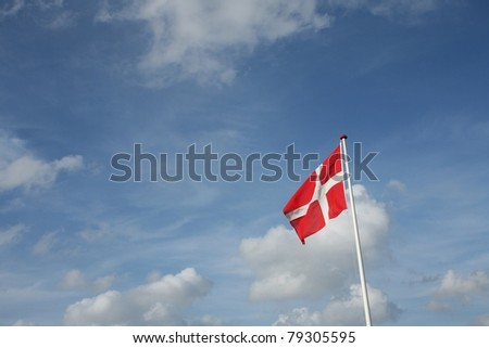 Danish flag in the wind with blue sky - stock photo