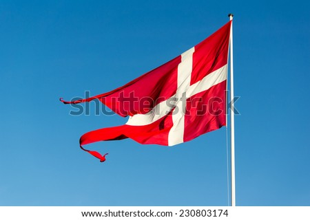 Danish flag waving in strong wind against blue sky - stock photo