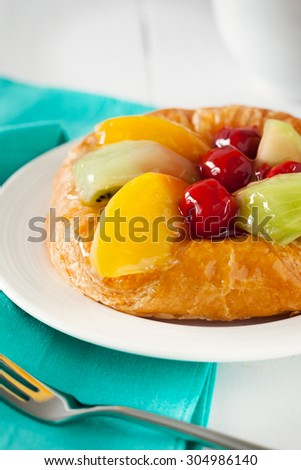 danish pastry with fruit on plate - stock photo