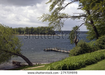 Danish windy landscape by the Little Belt with two men standing paddling on surfboards - stock photo
