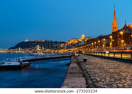 Danube waterfront in Pest with a view over Chain Bridge and Buda Castle at night, Budapest, Hungary. Caption on the walkaway has pattern with Chain Bridge, which was taken from the image itself.  - stock photo