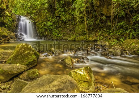 Dappled light on a waterfall and stream in a forest clearing in Costa Rica. - stock photo