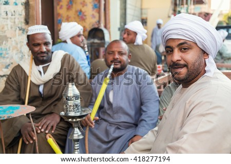 DARAW, EGYPT - FEBRUARY 6, 2016: Local men smoking shisha pipe at Daraw market. - stock photo