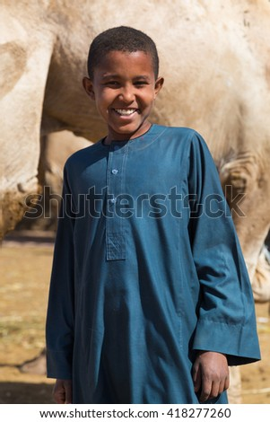 DARAW, EGYPT - FEBRUARY 6, 2016: Local young camel salesmen on Camel market posing for camera. - stock photo