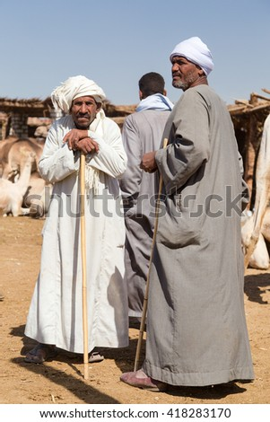 DARAW, EGYPT - FEBRUARY 6, 2016: Portrait of elderly camel salesmen with stick at Camel market. - stock photo