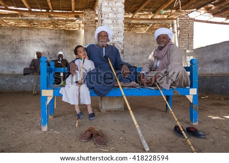 DARAW, EGYPT - FEBRUARY 6, 2016: Two elderly camel salesmen and little boy sitting on the bench at Camel market. - stock photo