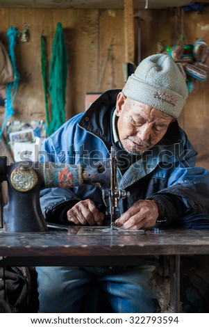 Darjeeling, India- April 15, 2011: An old refugee male working hard ,sewing, making souvenir for tourists in a refugee camp.