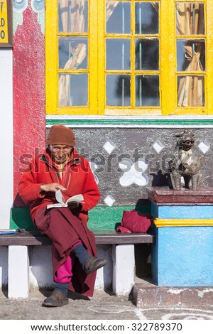 Darjeeling, India- April 15, 2011: Faithful male lama dress in red sitting in front of a monastry wall reading a prayer book.