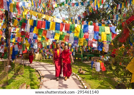 DARJEELING, INDIA - APRIL 14: Tibetan monks walk through a temple pathway surrounded by colorful tibetan prayer flags on April 14, 2014 in Darjeeling, West Bengal, India.