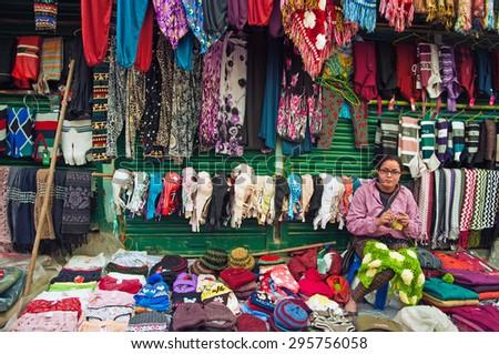 DARJEELING, INDIA - APRIL 14: Tibetan woman weaves colorful woolen garments for sale at Darjeeling Mall Chowrasta market on April 14, 2014 in Darjeeling, West Bengal, India. - stock photo