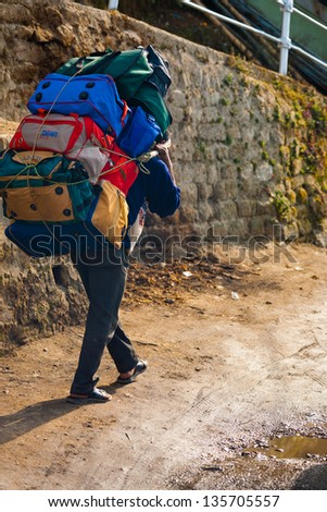 Darjeeling, India - December 26, 2007: Indian man porter carrying a many heavy bags uphill using strap around his head, leaning forward due to the load