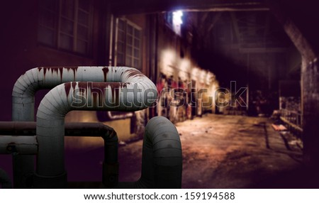 Dark alley with rusty pipes in foreground - stock photo