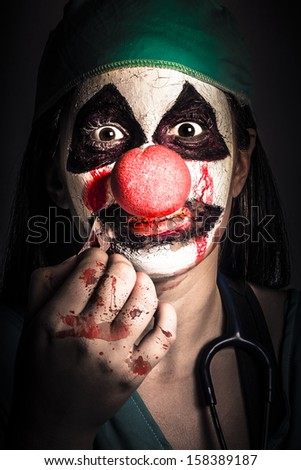Dark and creepy medical portrait of a horror clown girl expressing fear in silence when removing band aid to reveal lips sown shut. Medical conspiracy