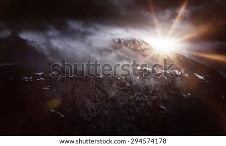 Dark and Dramatic Panoramic Scenic View of Bright Sun Peeking Over Ridge of Snow Capped Rugged Mountains, Berchtesgaden, Bavarian Alps, Germany